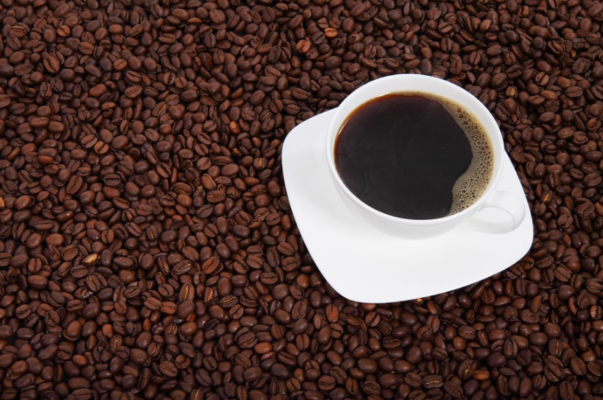 a cup of black coffee, and coffee beans