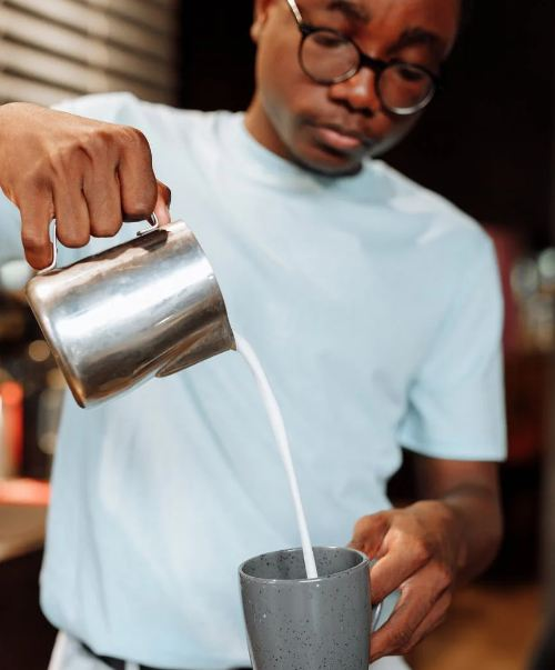 A person pouring milk in coffee